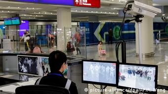 Работник санитарной службы в аэропорту Гонконга отслеживает на мониторах данные тепловизоров