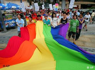 Young participants wave rainbow-colored flag, a symbol of the gay rights movement during a parade in downtown Hong Kong