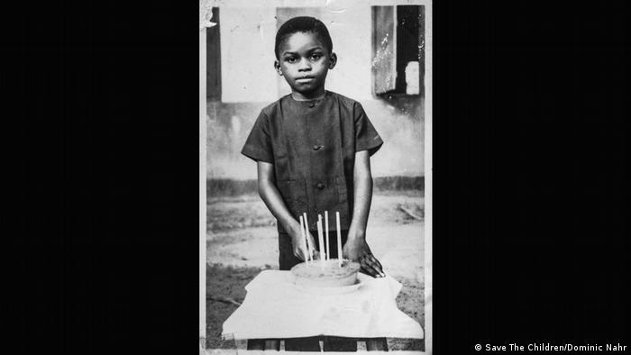 Ein Schwarz-Weiß-Foto eines Jungen mit einem Kuchen, auf dem sechs Kerzen oder Stäbe stecken (Foto: Save The Children/Dominic Nahr)