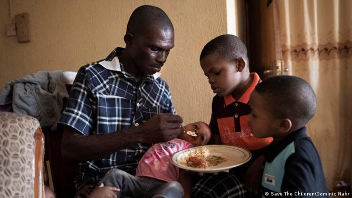 Amadi füttert ein Kind, zwei weitere stehen daneben (Foto: Save The Children/Dominic Nahr)