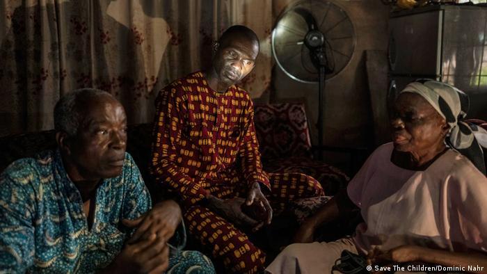 Zwei Männer und eine Frau sitzen in einem Haus im Halbdunkel beisammen. (Foto: Save The Children/Dominic Nahr)