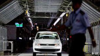 A security man walks past a Volkswagen Polo at its new factory in Chakan, near Pune, India, Saturday, Dec. 12, 2009. Volkswagen AG started production of its first compact car in India on Saturday, hoping to capture up to 10 percent of the country's fast-growing automobile market within the next six years, the company said. The factory, opened earlier this year, is part of a 580 million euros (US$846.8 million) investment, which the company says is a key element in its India strategy. (AP Photo/Rafiq Maqbool)