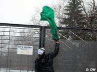 جوانی در حال افکندن پرچم سبز به داخل کنسولگری جمهوری اسلامی