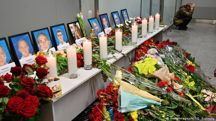 Цветы и горящие свечи у фотоснимков погибших в катастрофе украинского самолета в Иране