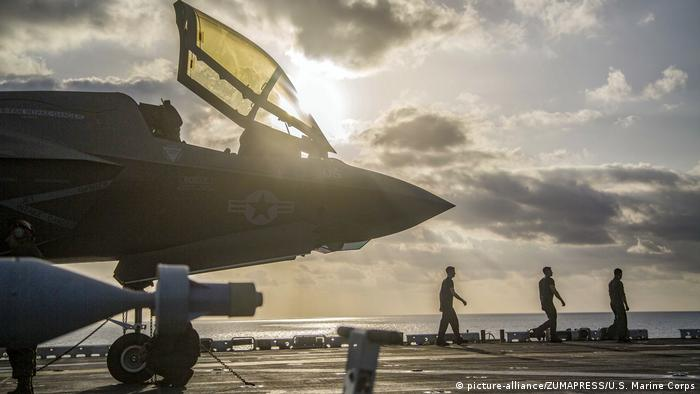 A Marine Corps F-35B Lightning II sits on the flight deck of the Wasp-class amphibious assault ship USS Essex (LHD 2) while Marines with Marine Fighter Attack Squadron 211, 13th Marine Expeditionary Unit (MEU), prepare for flight operations