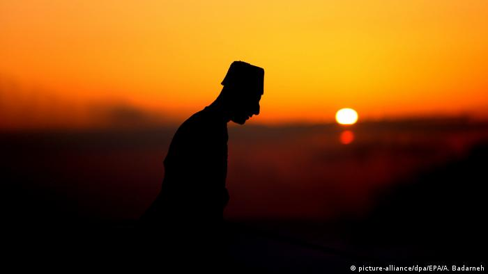 Silhouette of a man with a setting sun in the background