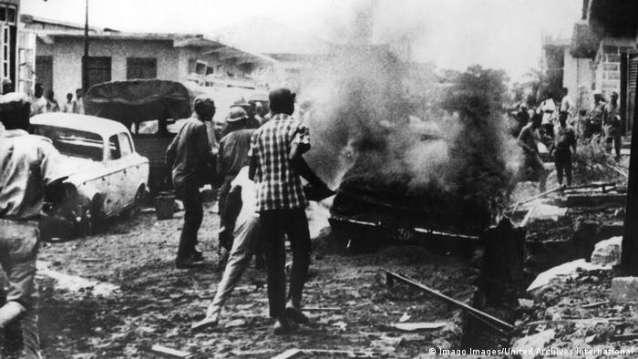 Menschen stehen auf einer Straße neben Autowracks und einer Rauchwolke (Foto: Imago Images/United Archives International)