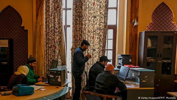 Kashmir students use the internet at a government-controlled kiosk