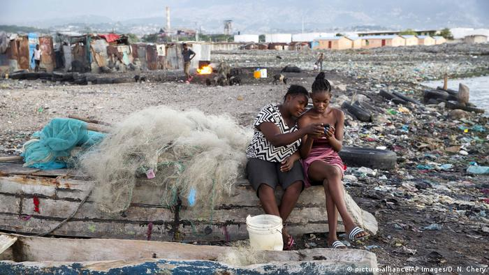 Two friends on a trash-littered beach in a Port-au-Prince slum (picture-alliance/AP Images/D. N. Chery)