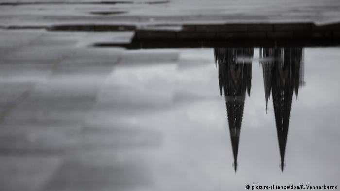 Reflection of Cologne Cathedral in a puddle