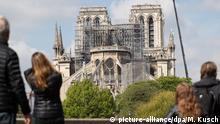 ARCHIV - 17.04.2019, Frankreich, Paris: Ein Kran steht neben der Pariser Kathedrale Notre-Dame, die von Besuchern der Stadt betrachtet wird. Das Feuer vom Montag (15.04.2019) hatte die Kathedrale stark zerstört. Barbara Schock-Werner, Koordinatorin der deutschen Hilfe für den Wiederaufbau von Notre-Dame, plädiert für neuen Dachstuhl aus Stahl. Foto: Marcel Kusch/dpa +++ dpa-Bildfunk +++ | Verwendung weltweit