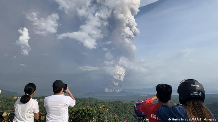 Spectators view the plume of ash of the Taal Volcano
