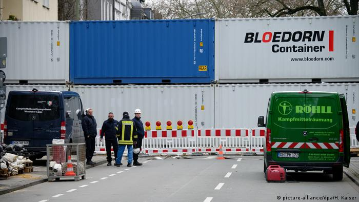 Containers stacked across a Dortmund inner-city street