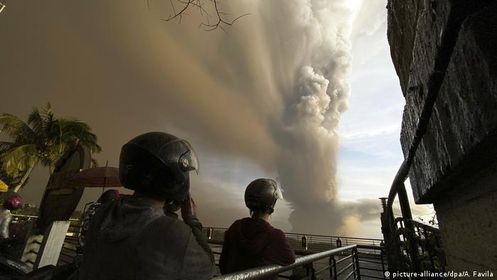 People watch plumes of smoke and ash rise from Taal Volcano