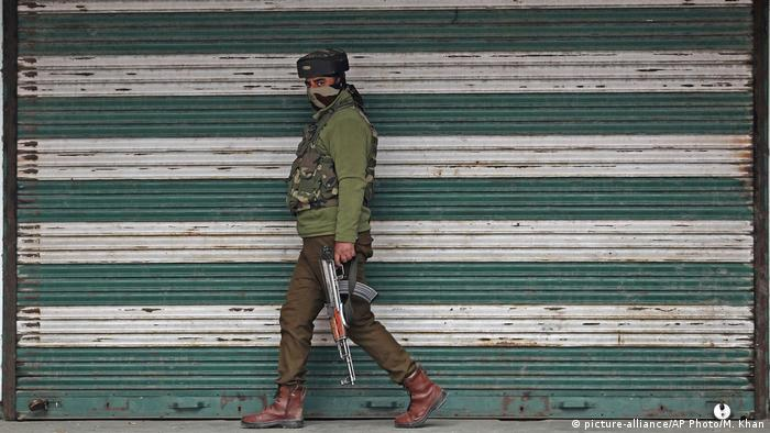 An Indian policeman patrols near the site of an explosion at a market in Srinagar, Indian controlled Kashmir
