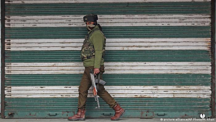 An Indian policeman patrols in Srinagar