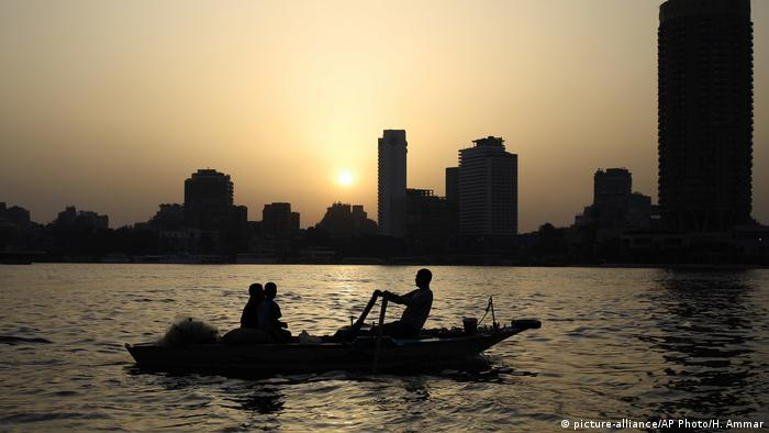Egyptian fisherpeople fish on the Nile River as the sun sets in Cairo, Egypt