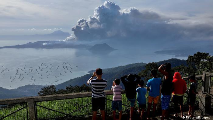 Pessoas tiram foto de um vulcão enquanto fumaça sobe no horizonte