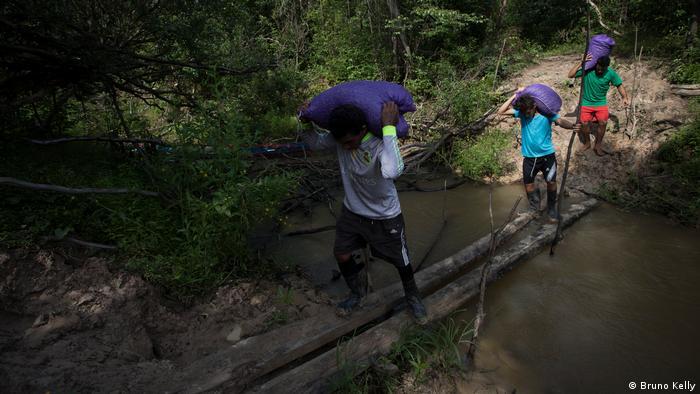 Pessoas caminhando sobre córrego numa floresta carregando sacos na cabeça