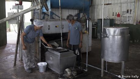Duas pessoas junto a uma prensa de óleo