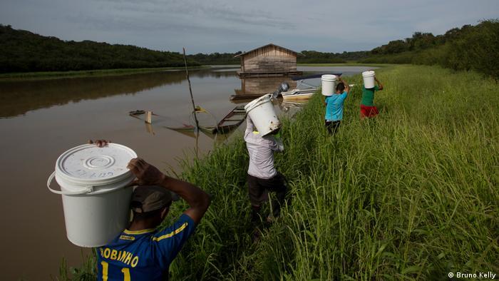 Pessoas caminhando em margem de rio carregando baldes brancos na cabeça