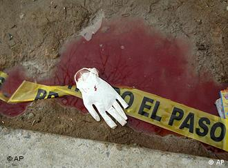 A surgical glove lies on a puddle of bloodied water outside of a home where unknown gunmen a day earlier stormed a gathering of students, killing at least 13 and injuring dozens in the northern border city of Ciudad Juarez, Mexico, Sunday Jan. 31, 2010. (AP Photo)