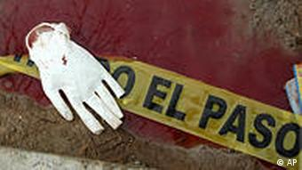 A surgical glove lies on a puddle of bloodied water outside of a home where unknown gunmen stormed a gathering of students, killing at least 13 in Ciudad Juarez