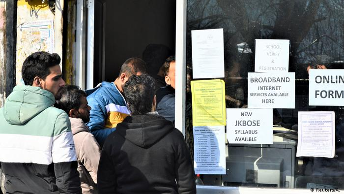 People line up to use the internet at a cafe in Kashmir