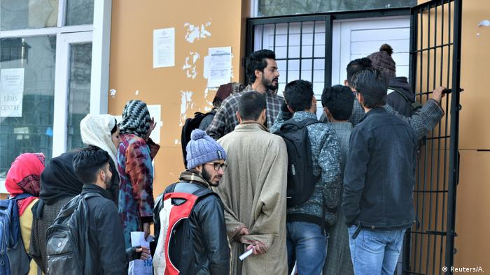 People queue up to go online at a government set-up internet cafe in Budgam.