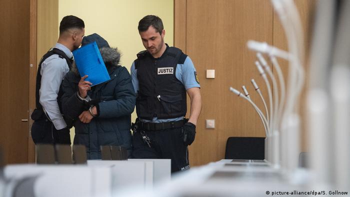 Police escort a defendant in the case