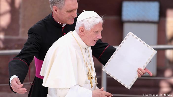Papa emérito Bento 16, de branco, guiado por seu secretário particular