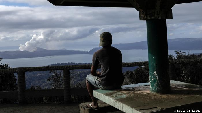 A man in the Philippines watches as a plume of ash rises from the distant Taal Volcano