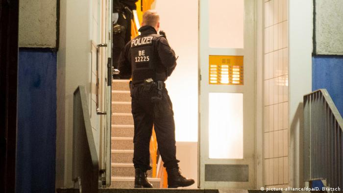A police officer takes part in a raid at an apartment building in Berlin, Germany