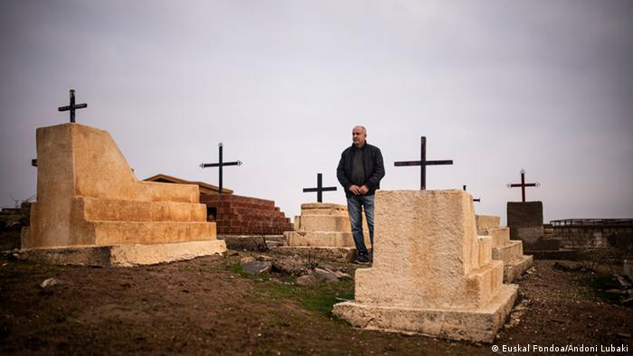 A man standing next to graves