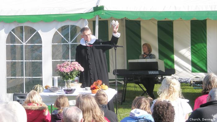 A priest holding a flower and preaching in front of a group of people