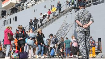 People evacuating Mallacoota leave a military ship