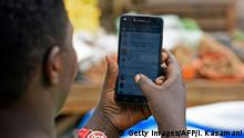 A woman is seen going through her WhatsApp account on her phone in Kampala on July 5, 2018. - Politicians, clerics, feminists and others have formed a broad coalition of Ugandans calling for an end to a social media tax the government hopes will raise revenue and silence gossip. On July 1, 2018, Uganda's communications regulator blocked access to social media including WhatsApp, Facebook and Twitter, as well as dating sites Tinder and Grindr, unless users pay a 200-shilling (USD 0.05, 0.04 euro) daily tax. The outcry was immediate. (Photo by Isaac Kasamani / AFP) (Photo credit should read ISAAC KASAMANI/AFP via Getty Images)