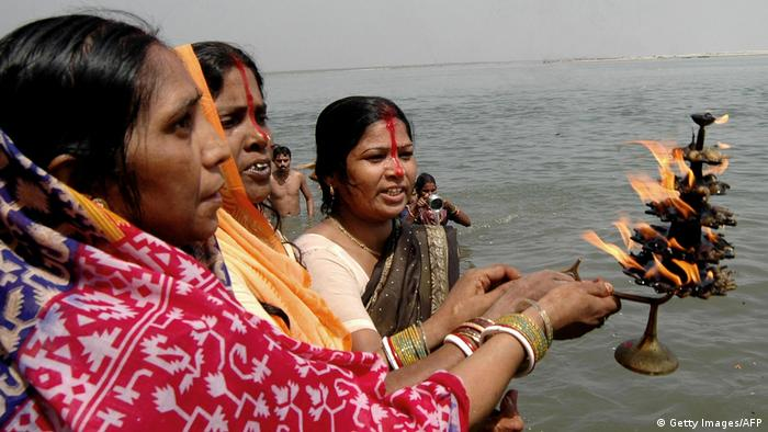 Indian Hindu devotees hold a lamp as they pray in celebration of the'Ganga Dussehra' Festival on the banks of the River Ganges at Patna