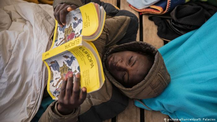 Un joven de Mali rescatado por el Open Arms lee un libro sobre Europa a bordo del barco humanitario.