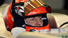 Mercedes Formula One driver Michael Schumacher of Germany prepares to drive his car out of the team's pit garage during a testing session at the Ricardo Tormo race track in Cheste, just outside Valencia, Spain, Monday, Feb. 1, 2010. (AP Photo/Paul White)