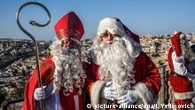 Wolfgang Pomp als Weihnachtsmann verkleidet und Peter Lenz im Kostüm des Nikolaus mit Bischofsmütze und Bischofsstab (picture-alliance/dpa/I.Yefimovich)