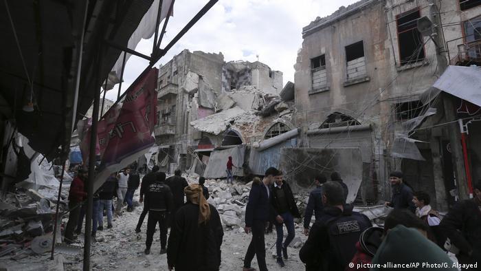 سوريون يتحركون وسط أنقاض منازل لحق بها دمار بمدينة أريحا في منطقة إدلب بعد تعرضها لهجوم جوي من قبل القوات الحكومية. (15 يناير/ كانون الثاني 2021)