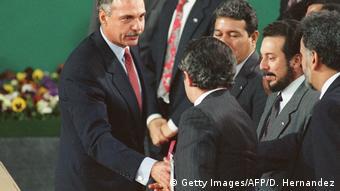 Foto de expresidente Alfredo Cristiani mientras saluda a exguerrilla del FMLN.