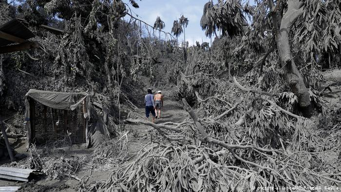 Two people walk through an ash-covered village after the Taal volcano erupted