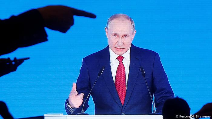 Russian President Vladimir Putin is seen on screen as he delivers his annual state of the nation address to the Federal Assembly
