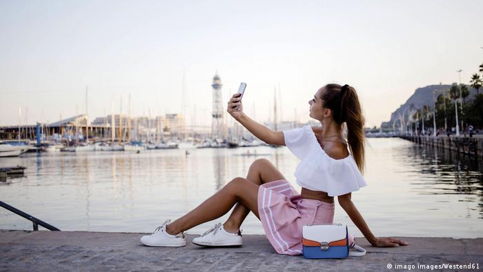 Young woman sitting on a harbor wall taking a smartphone picture of herself in Barcelona, Spain