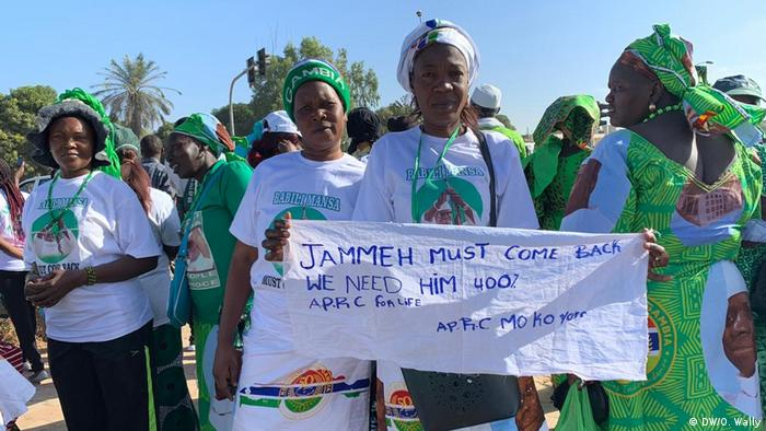 Supporters of Yahya Jammeh hold up a sign saying: 'Jammeh must come back. We need him.'