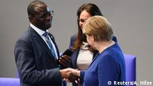 Chancellor Angela Merkel shakes hands with Social Democratic Party (SPD) Parliament Member Karamba Diaby during a plenum session on organ donation at the lower house of parliament, Bundestag, in Berlin, Germany, January 16, 2020. REUTERS/Annegret Hilse