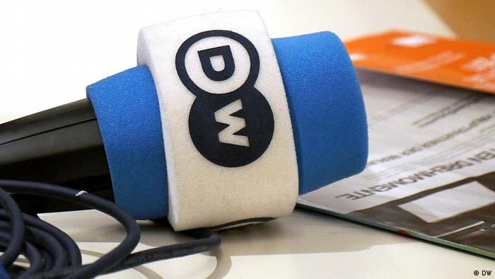 A DW microphone rests on a table