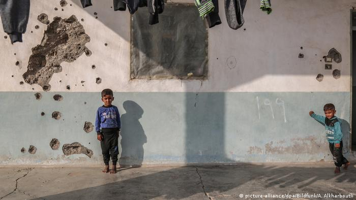 Two kids in front of a wall damaged by shelling
